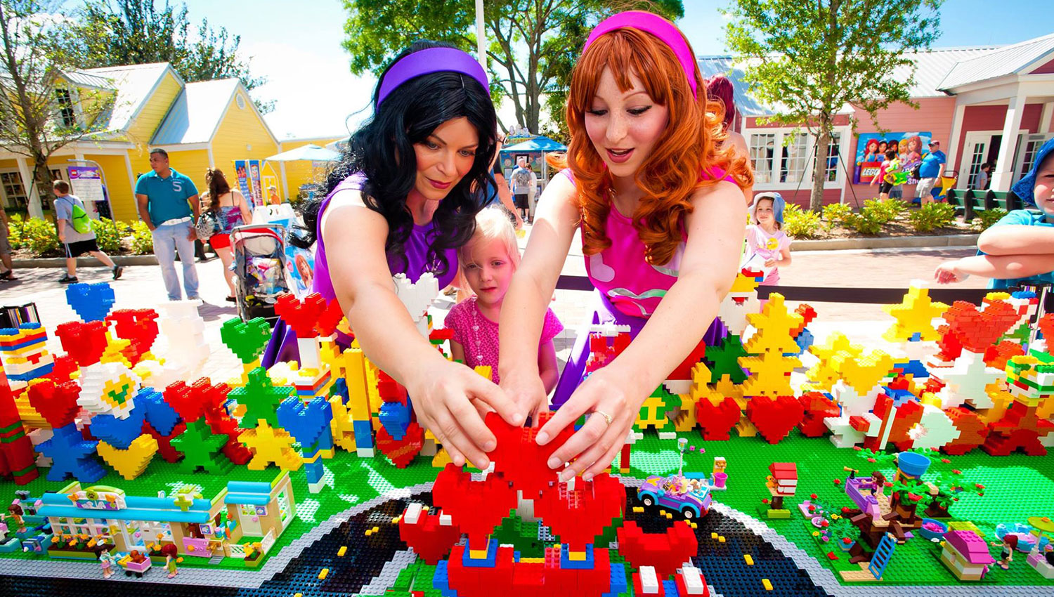 blond child watches lego being built by two women