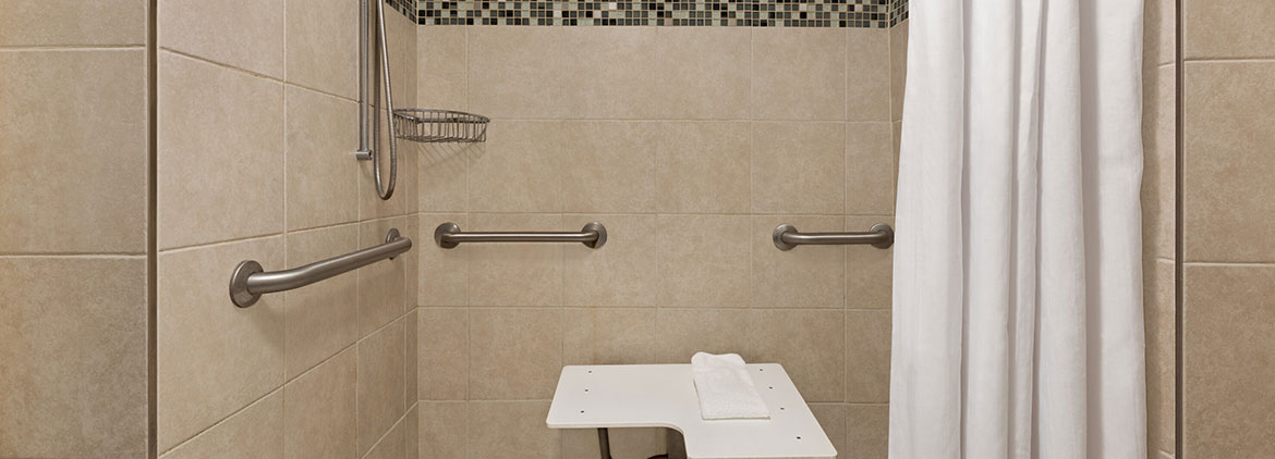 white towels and toliet and easily accessible shower with a sitdown seat