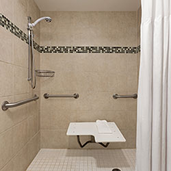 ADA accessible suites with white shower background and bath seat
